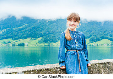 Outdoor portrait of a cute little girl in jeans dress against beautiful lake