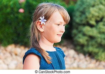 Outdoor portrait of a cute little girl in profile