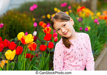 Outdoor portrait of a cute little girl of 7 years old, wearing pink jacket, sitting next to tulips