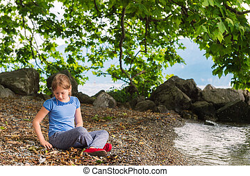 Outdoor portrait of a cute little girl on a nice sunny day, playing by the lake