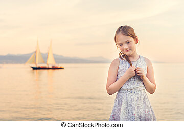 Outdoor portrait of a cute little girl playing by the lake at sunset, toned image