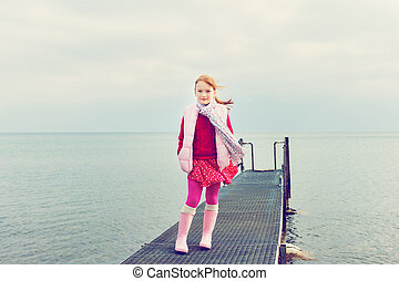 Outdoor portrait of a cute little girl playing by the lake on a cloudy day, wearing red dress and pink vest, toned image