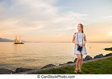 Outdoor portrait of a cute little girl playing by the lake on a nice warm evening