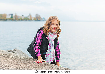 Outdoor portrait of a cute little girl playing next to lake on a fresh day