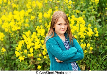 Outdoor portrait of a cute little girl playing with flowers in a countryside, wearing warm emerald knitted jacket