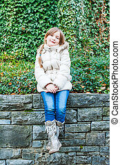 Outdoor portrait of a cute little girl sitting on a wall, wearing white warm jacket, jeans and boots