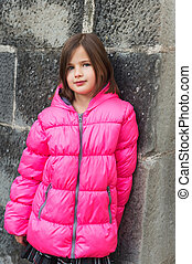 Outdoor portrait of a cute little girl wearing bright warm pink jacket