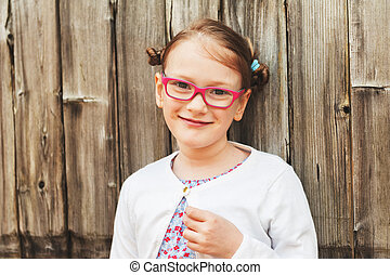 Outdoor portrait of a cute little girl wearing glasses