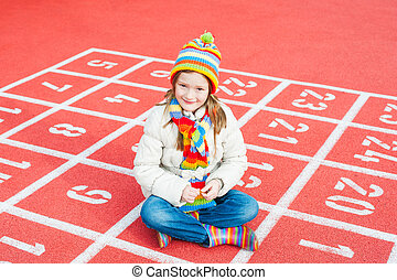Outdoor portrait of a cute little girl wearing jacket and colorful hat and scarf