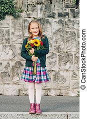 Outdoor portrait of a cute little girl wearing schoolwear, holding beautiful bouquet of autumn flowers