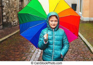Outdoor portrait of a cute little girl, wearing warm green jacket, holding big colorful umbrella