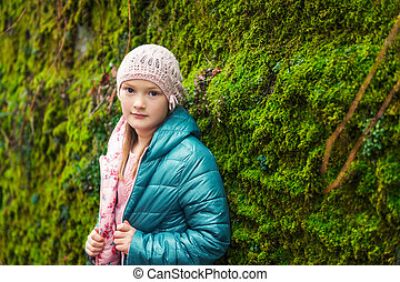 Outdoor portrait of a cute little girl wearing warm green jacket
