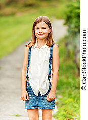 Outdoor portrait of a cute little girl wearing white shirt and denim skirt with suspenders