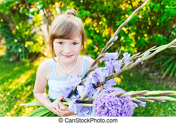 Outdoor portrait of a cute little girl with beautiful bouquet of purple flowers