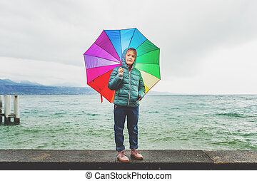 Outdoor portrait of a cute little girl with big colorful umbrella, playing by the lake on a cold rainy day