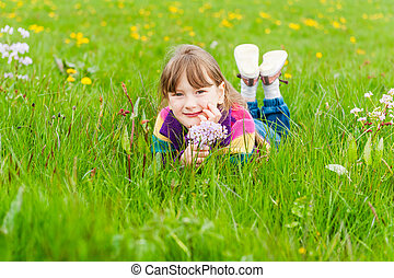 Outdoor portrait of a cute little girl with bouquet of wildflowers, laying in a field, wearing, colorful jacket