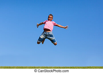 Outdoor portrait of a cute teenage black boy jumping over a blue sky - African people
