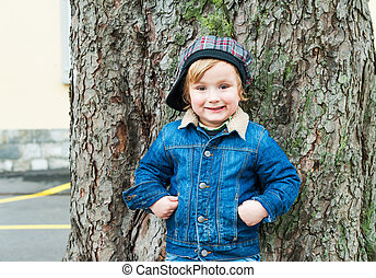 Outdoor portrait of a cute toddler boy wearing jeans jacket and a hat