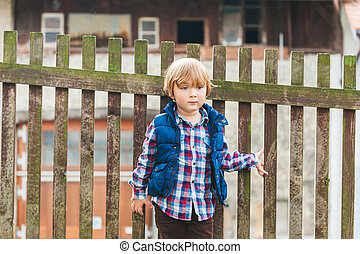 Outdoor portrait of a cute toodler boy resting in a countryside