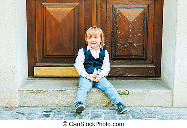 Outdoor portrait of a cute toodler boy, sitting on steps in a city, wearing beautiful celebration clothes