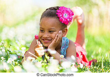 Outdoor portrait of a cute young black girl  lying down on the grass and smiling - African people