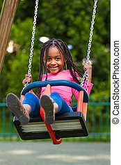 Outdoor portrait of a cute young black girl playing with a...