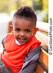 Outdoor portrait of a cute young  little black boy seated on a bench - African people