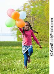 Outdoor portrait of a cute young  little black girl playing with balloons - African people