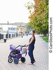 Outdoor portrait of a happy mother and son. Baby sitting in stroller