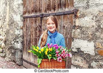 Outdoor portrait of a little girl with big basket full of many fresh colorful tulips