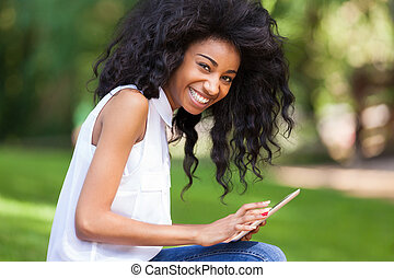 Outdoor portrait of a smiling teenage black girl using a tactile tablet - African people