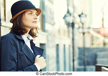 outdoor portrait of a stylish woman with hat in street