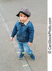 Outdoor portrait of a toddler boy, wearing denim clothes
