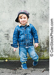 Outdoor portrait of a toddler boy, wearing jeans clothes