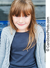 Outdoor portrait of adorable little girl in a city