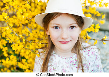 Outdoor portrait of adorable little girl in a hat
