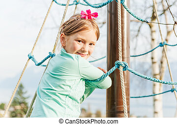 Outdoor portrait of adorable little girl playing in a park