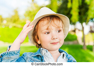 Outdoor portrait of adorable toddler boy on a nice sunny day, wearing a hat
