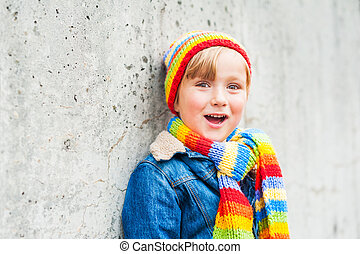 Outdoor portrait of adorable toddler boy wearing colorful hat and scarf