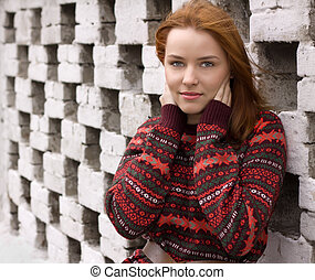 Outdoor portrait of beautiful redhair woman in red sweater