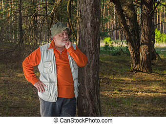 Outdoor portrait of Caucasian senior near pine tree