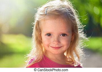 Outdoor portrait of cute little girl in summer day