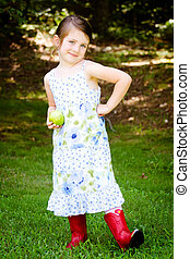 Outdoor portrait of cute young girl holding apple for healthy snack in park