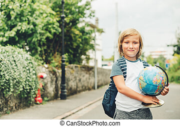 Outdoor portrait of funny little kid boy wearing backpack and holding world globe. Back to school concept. Film look filter image