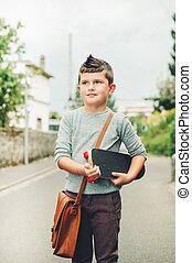 Outdoor portrait of funny little schoolboy wearing brown leather bag over shoulder, holding skateboard. Back to school concept. Film look toned image