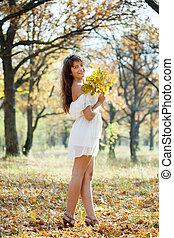 girl in white dress at autumn park