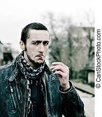 Outdoor portrait of handsome young man smoking cigarette