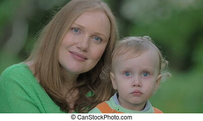 Outdoor portrait of happy mother and little son