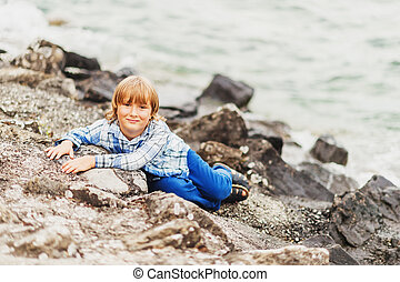 Outdoor portrait of little kid boy playing by the lake