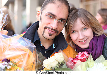 outdoor portrait of man in glasses and beauty blond girl with flower bouquets, looking at camera and smiling